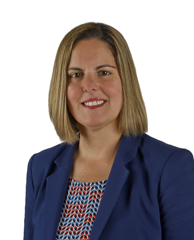 Branch Manager Sonia Estrela against white background wearing a blue blazer smiling