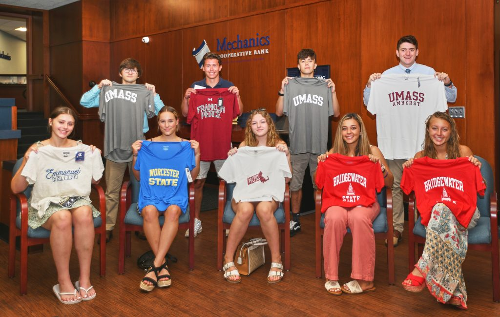 Scholarship recipients are pictured holding up t-shirts of the college they are attending in the fall. There are two rows of people pictured with the front row sitting in chairs.